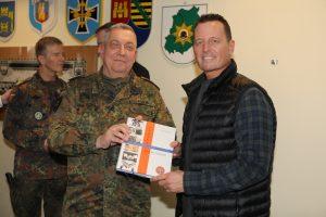 Zum Abschluss überreichte der Vorsitzende RK Ost, Oberst Adrian, Botschafter Grenell ein Buch zum Baushausjubiläum